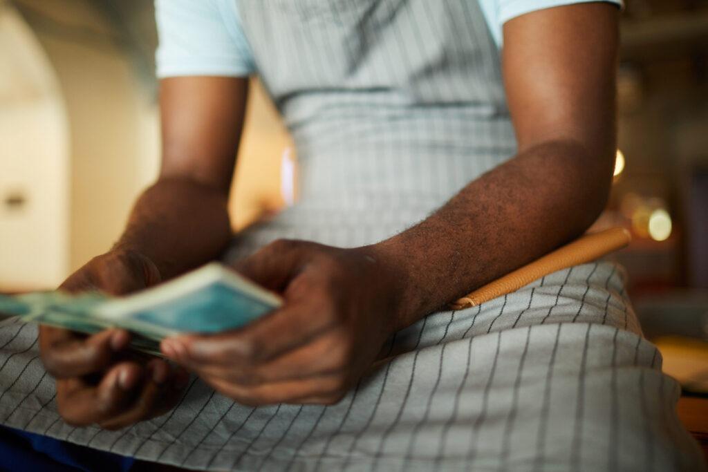איש בפיג'מה סופר כסף על המיטה